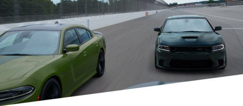 Green and black Dodge Charger on the track