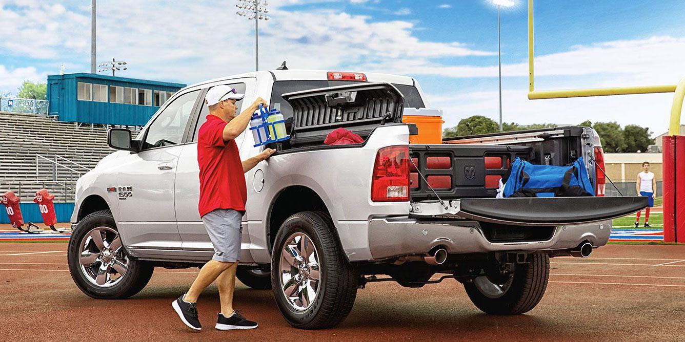 football player loading sport gear on his white ram truck slt