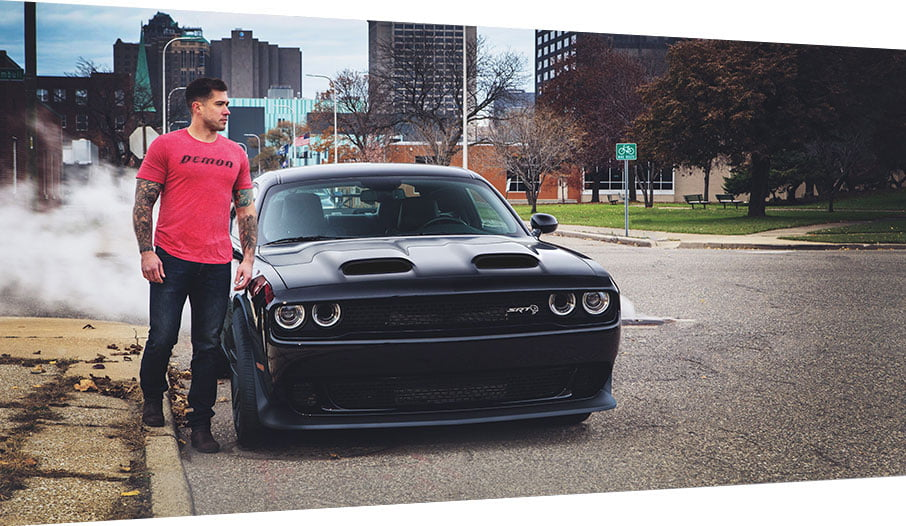 man standing next to dodge challenger demon black